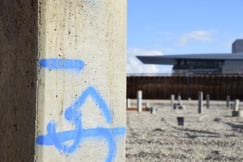 Papirøen - Christiansholm Ø. Nedrammede pæle stikker op af jorden. Operaen i baggrunden.