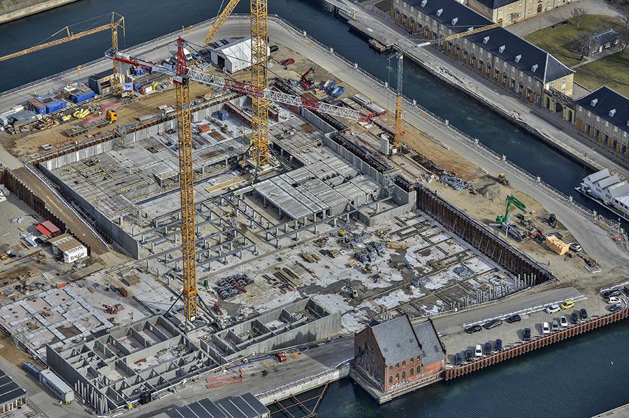 PAPIRØEN - luftfoto over byggeplads. Kraner element montage til parkeringskælder i byggegruben.