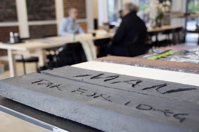 Petersen Tegl, showrrom. Stemningsbillede - to mænd ved mødebord sløret i baggrunden. Forgrund billede af tegl, hvor der er ridset 'Tak for i dag' ind, mens leret var blødt.