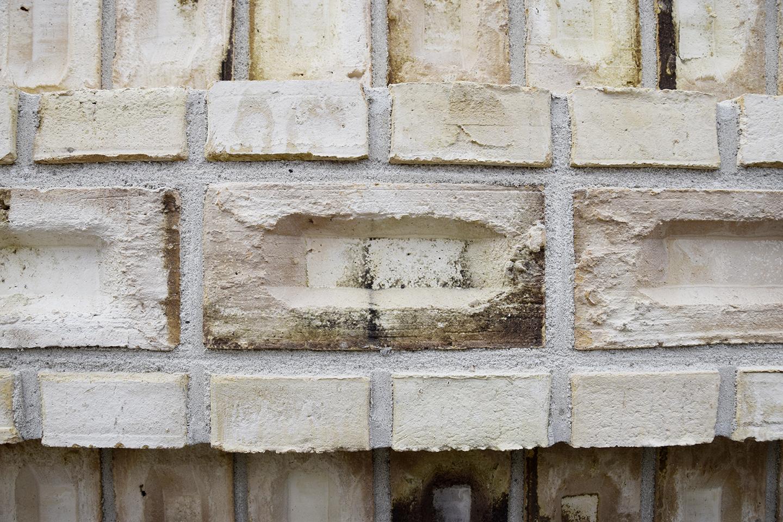 PAPIRØEN - nærbillede af opmuret væg med Christiansholmerstenen