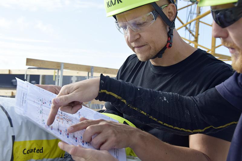 Papirøen - to mænd ser på byggetekniske tegninger.